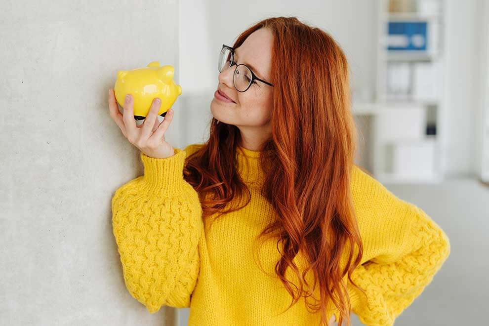Woman holding a piggy bank looking happy