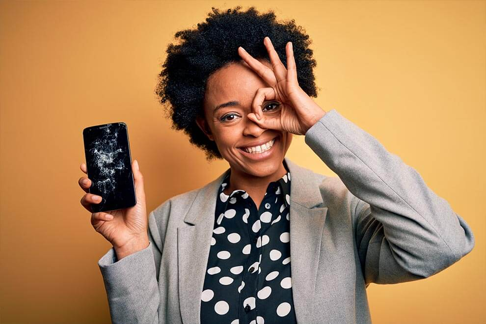 Woman smiling despite holding broken smartphone