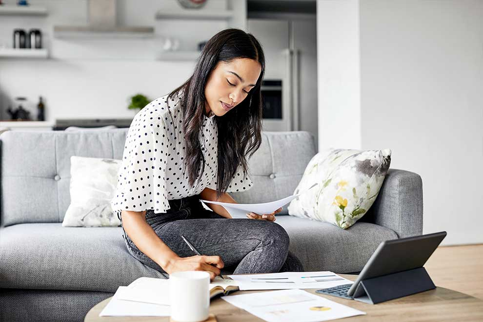 Woman working on papers and laptop at coffee table